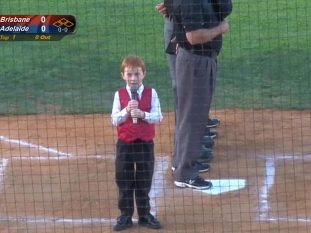 Un copil adorabil sughițând în timp ce cântă imnul național